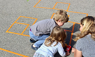 Mother and children building tape maze on playground